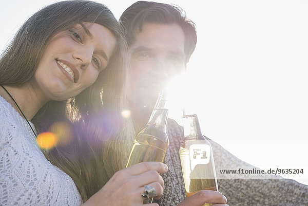 Portrait young couple sunset drinking beer