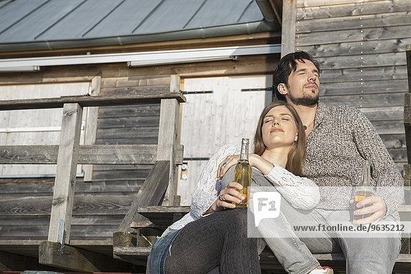 Man woman relaxing sunbathing jetty drinking beer