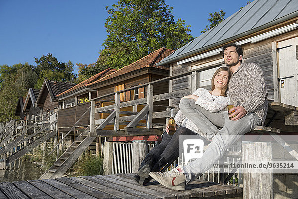 Young couple relaxing jetty drinking beer