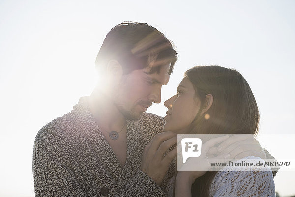 Romantic sunset young couple embracing