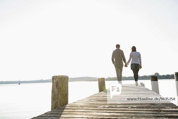 Couple walking on wooden jetty sunset