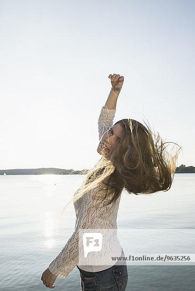 Young pretty woman dancing sunset lake