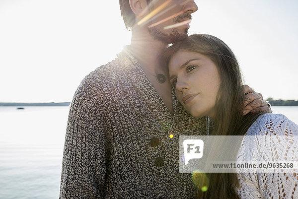 Young couple hugging sunset lake