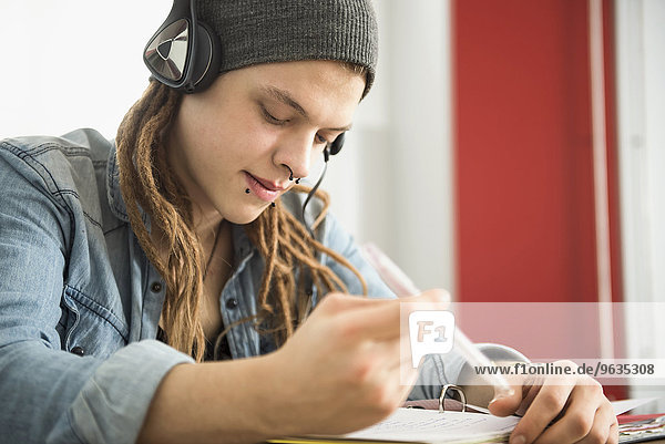 Young man wearing headphones and studying at home