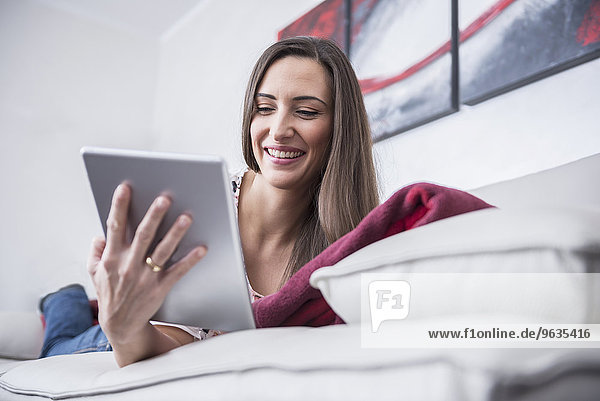 Beautiful woman lying on couch and using a digital tablet