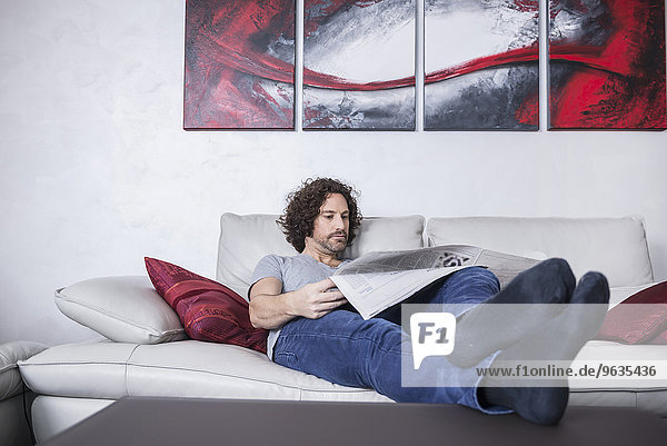 Man lying down on couch and reading a newspaper