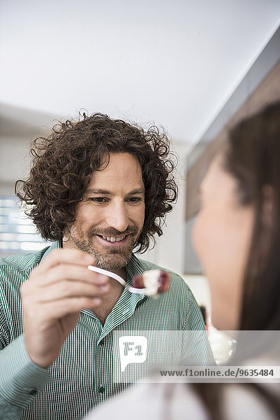 Man feeding slice of cake to his wife Man feeding slice of cake to his wife