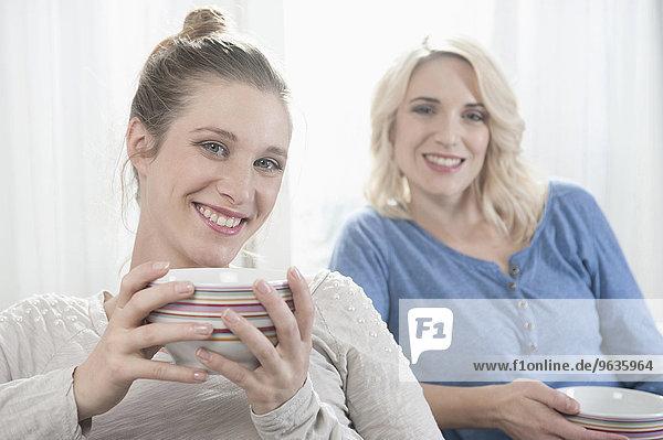Portrait two women tee drinking smiling girlfriend