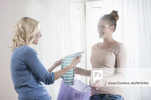 Pregnant woman girlfriend baby clothes holding