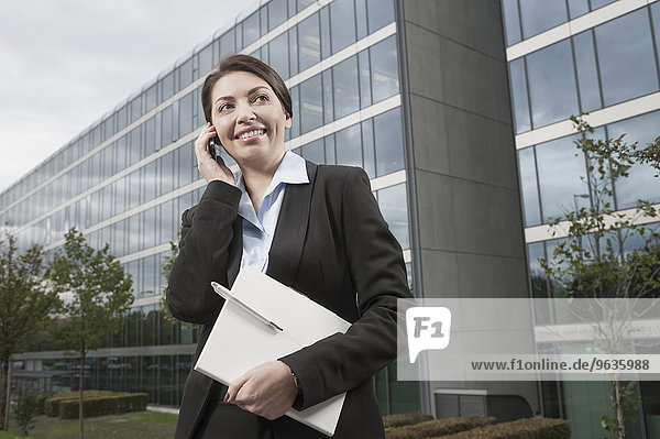 Attractive businesswoman speak a cell phone standing in front of a modern office building