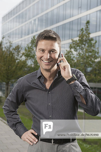 Smart businessman speak a cell phone standing in front of an office building