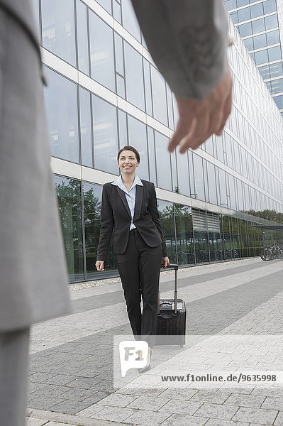 Businessman's hand greeting businesswoman at her arrival