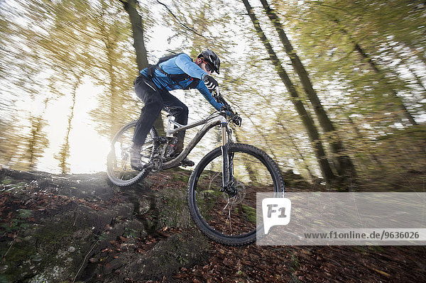 Mountain biker riding downhill in a forest