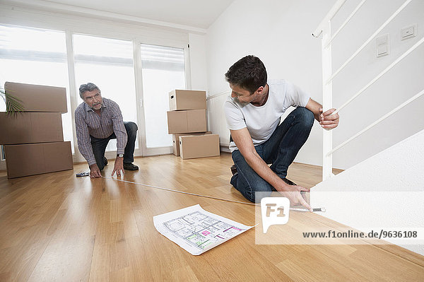 Father and son measuring wooden floor in new home