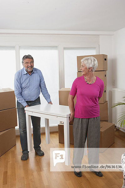 Senior couple moving a table in new apartment