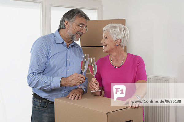 Senior couple moving into new home celebrating with champagne