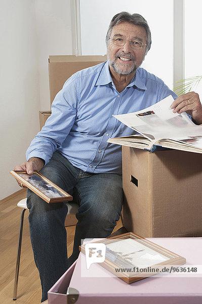 Senior man with photo album in new apartment