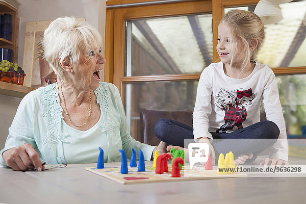 Girl playing board game with her grandmother