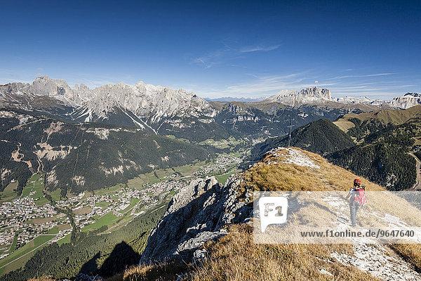 Bergsteiger beim Aufstieg auf die Cima Dodici  Sas da le Doudesh im Val San Nicolo  hinten die Rosengartengruppe  Langkofel und Plattkofel  unten das Fassatal und die Ortschaft Pozza di Fassa  Dolomiten  Trentino-Südtirol  Italien  Europa
