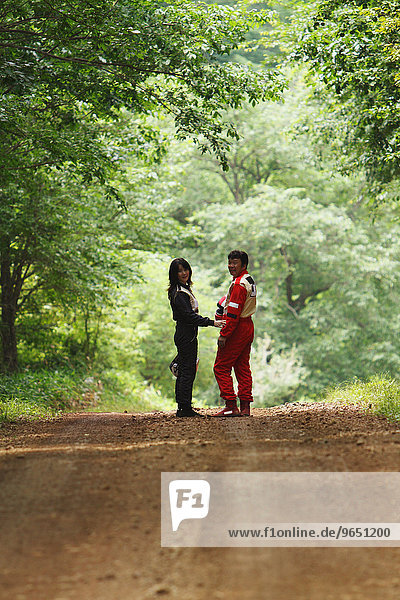 Rally drivers walking on dirt road in the woods