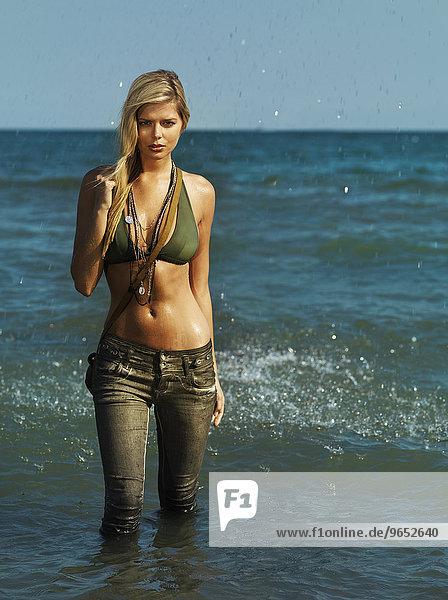 Junge Frau mit Jeans und Bikini-Oberteil steht im Wasser