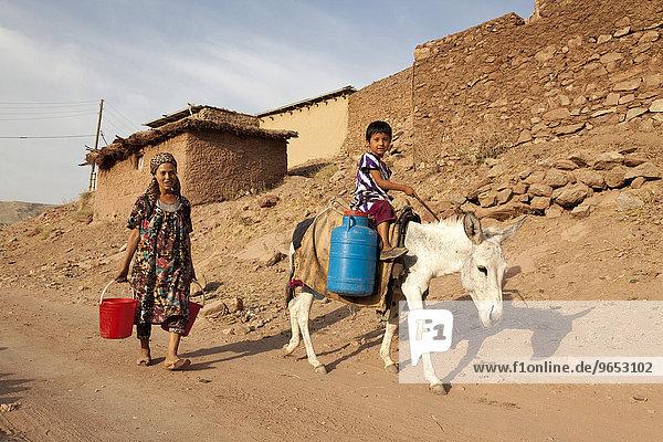 Frau und Junge auf einem Esel beim Wasserholen  Dorfleben  Usbekistan  Asien