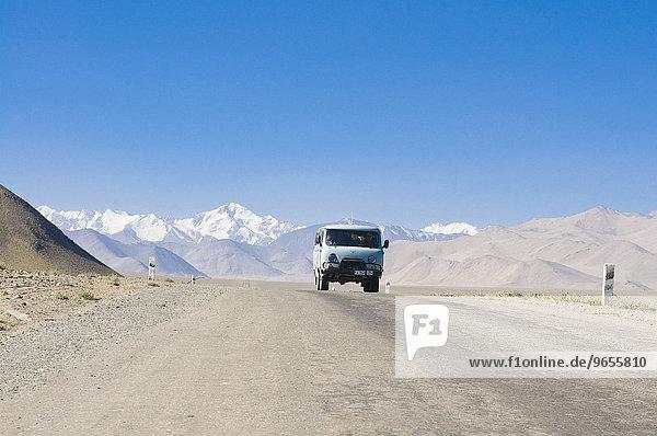 Landstraße führt zu schneebedecktem Gebirge  Karakul  Pamirgebirge  Tadschikistan  Zentralasien  Asien