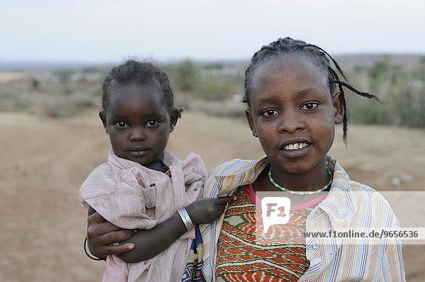 Junges muslimisches Mädchen trägt ein kleines Kind  Yabello  Südäthiopien  Äthiopien  Afrika