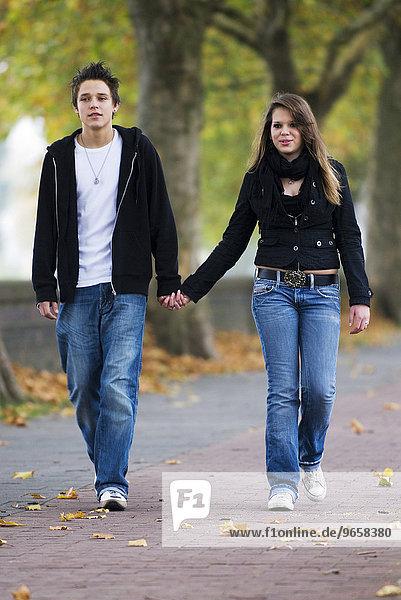 16-year-old teenage couple walking hand in hand