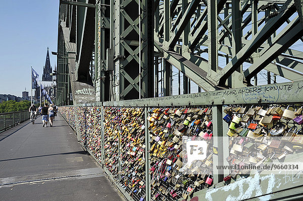 Love padlocks on security grid that separates the footpath from the railway tracks on Hohenzollern Bridge  Cologne  North Rhine-Westphalia  Germany  Europe