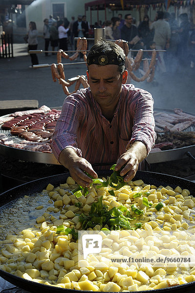 Cook adds pieces of green peppers to a large pan containing potato stew at the annual All Saints Market in Cocentaina  Alicante province  Spain  Europe