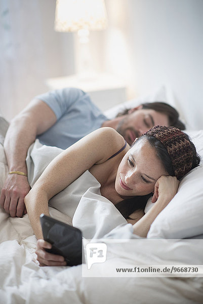 Frau Mann schlafen Tablet PC vorlesen