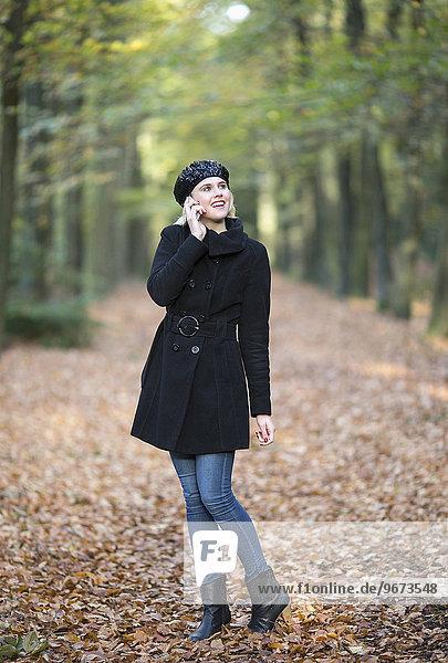 Frau lächeln gehen Wald telefonieren