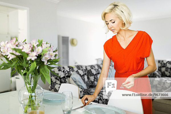 Woman in red dress setting the table