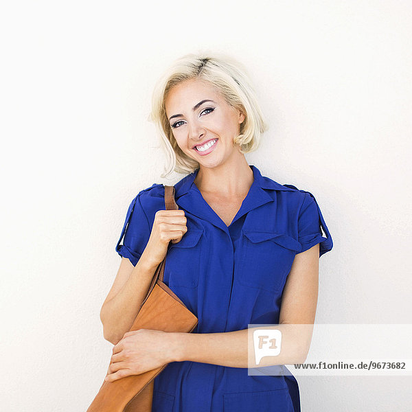Woman in blue dress and with leather bag posing to camera
