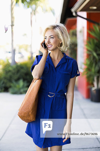 Woman in blue dress outside building using phone