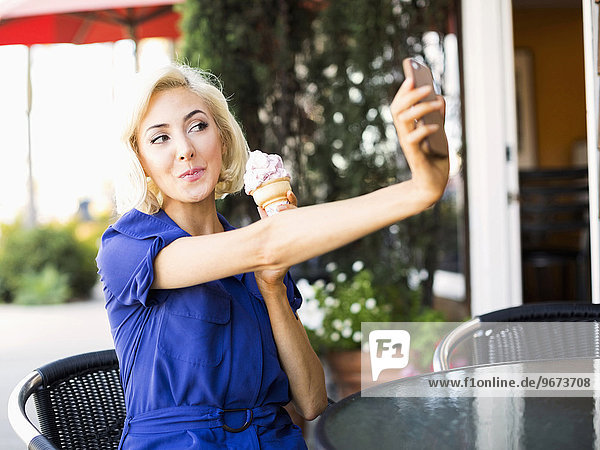 Woman photographing herself with ice-cream