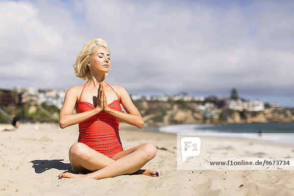 Portrait of blond woman on beach practicing yoga