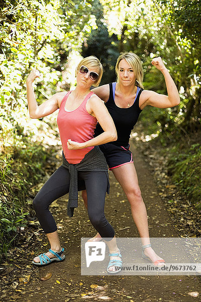 Two woman flexing muscles in forest