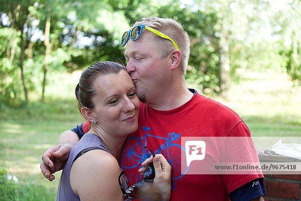 Mann Fröhlichkeit Ehefrau Liebe umarmen küssen Mittelpunkt