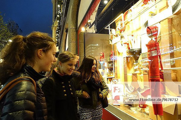 Young girls looking at Christmas decorations in the window of NK department store  Stockholm  Sweden