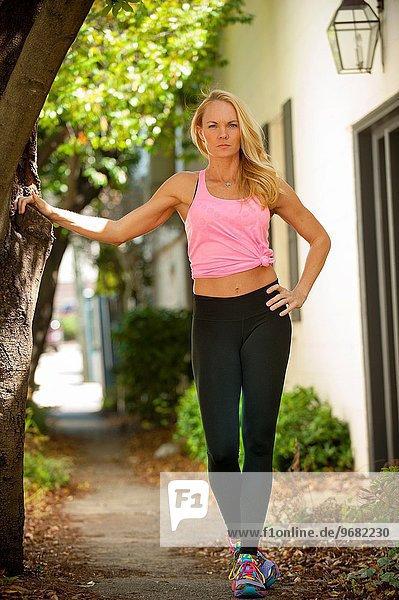 stehend Gesichtsausdruck Gesichtsausdrücke Ausdruck Ausdrücke Mimik blond Frau ernst Sport Kleidung 1 alt Jahr