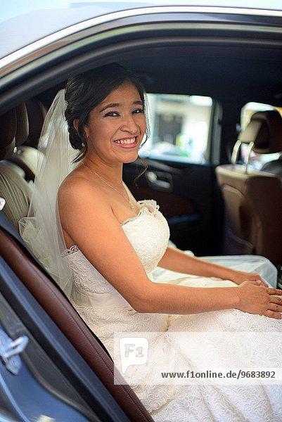 Latin bride in wedding car  nervous before the celebration.