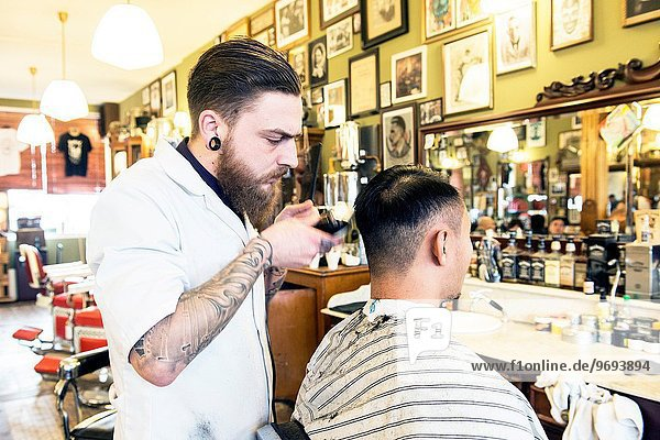 Rotterdam  Netherlands. Barber store Schorem. Barber helping his customer in his barber shop by cutting and modeling his hair.