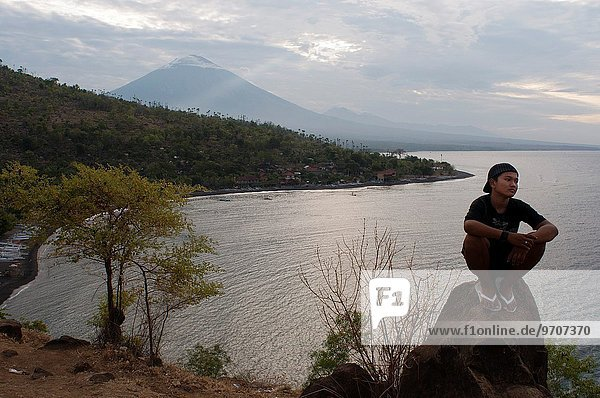 The small village of Amed fisherman with views of Mount Gunung Agung background (3142m). East Bali. Amed is a long coastal strip of fishing villages in East Bali. Amed refers to a long stretch of coast running from the village of Cucik about 14 km eastwards incorporating the seven villages of Amed  Jemeluk  Bunutan  Lipah  Selang  Banyuning and Aas. The pace of life here is slow and the coastal scenery quite stunning making Amed the perfect place for a relaxed holiday in Bali.