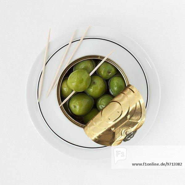Eine Dose grüne Oliven und Cocktailsticks