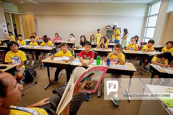 Showing a variety of expressions  Asia  Hispanic  and Caucasian middle school students listen to their teacher reading aloud to them at a writing project class in Irvine  CA. Note T shirts.