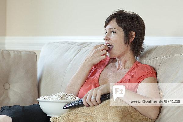 Europäer Frau sehen Fernsehen essen essend isst Popcorn