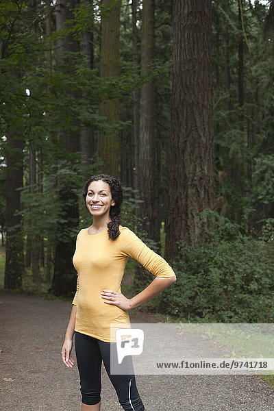 Smiling mixed race woman standing on path in forest