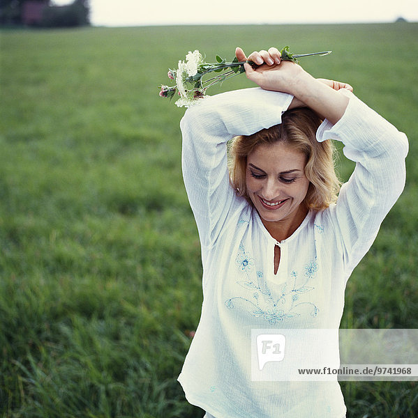 Caucasian woman standing in green field with flowers